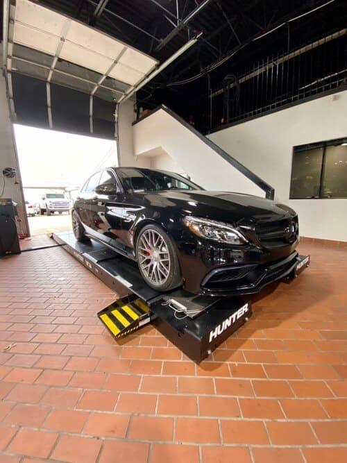 EurAuto Shop in Plano, Tx has a black Mercedes sedan on hunter alignment machine in shop bay